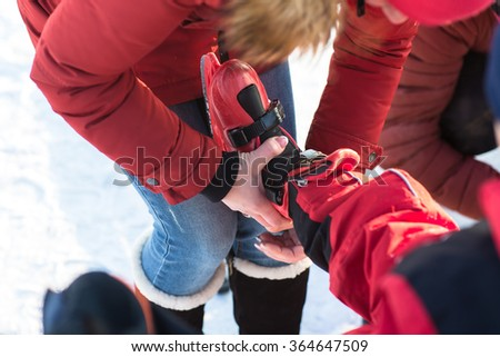 Parents put their children skating in winter on the street at the rink. Happy family skating. - stock photo