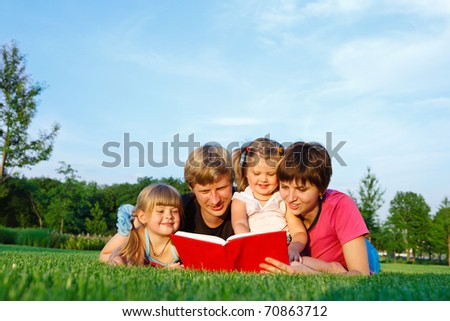 Parents reading a book to their daughters - stock photo