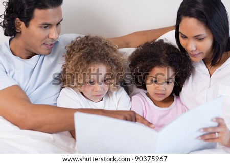 Parents reading a story for their young children - stock photo