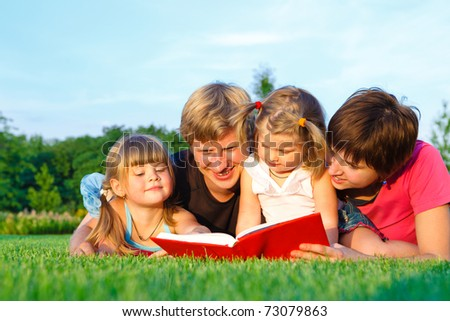 Parents reading book to their sweet offsprings - stock photo