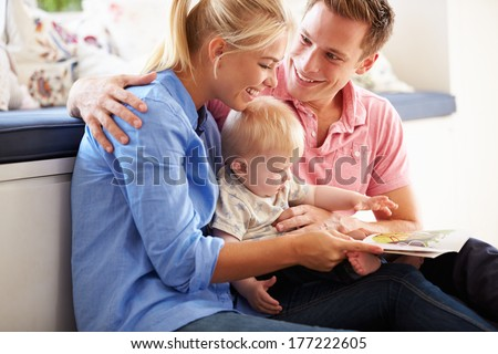 Parents Reading Book To Young Son - stock photo