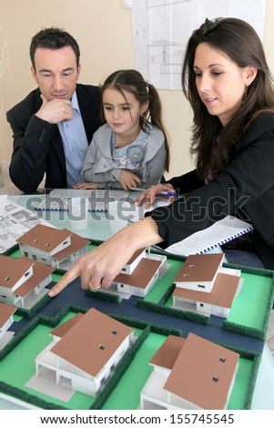 Parents showing daughter new house plans - stock photo