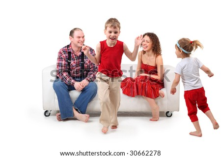 Parents sit on white leather sofa and look at running children - stock photo