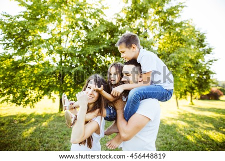 Parents Sitting With Children In Field Of Summer Flowers.Happy family having weekend in summer park - stock photo
