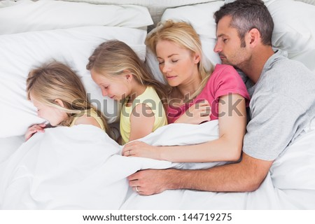 Parents sleeping in bed with their cute twins - stock photo