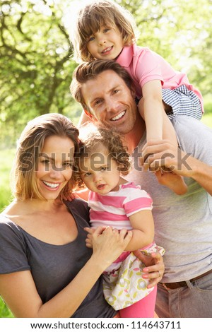 Parents Standing With Children In Field Of Summer Flowers - stock photo