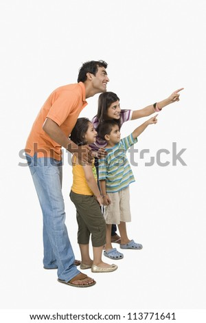 Parents standing with their children and pointing - stock photo