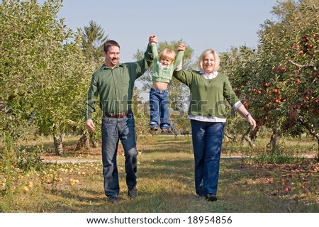 Parents Swinging Little Girl - stock photo