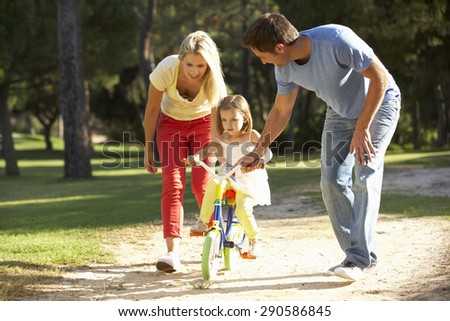 Parents Teaching Daughter To Ride Bike - stock photo