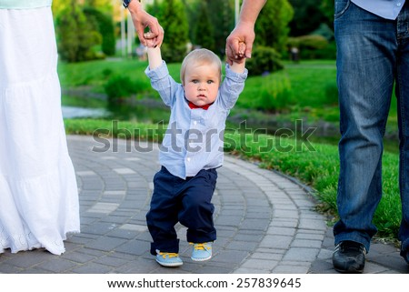 parents teaching their baby to making first steps - stock photo