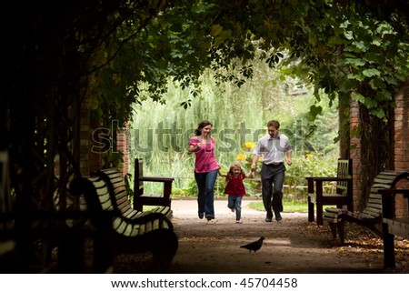 Parents together with daughter run on tunnel from ivy in summer garden. - stock photo