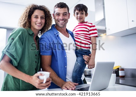 Parents using laptop with son in kitchen at home - stock photo