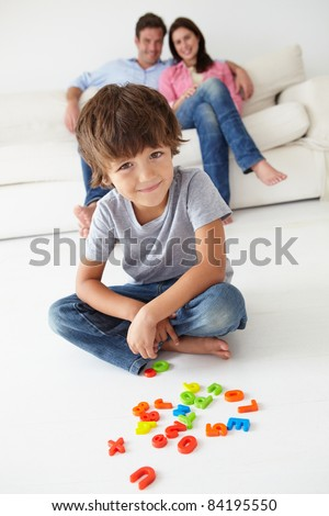 Parents watching son play - stock photo