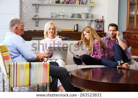 Parents With Adult Offspring Using Digital Devices At Home - stock photo