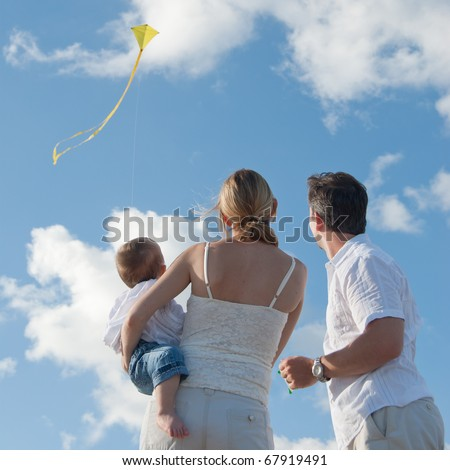 Parents with baby fly a kite in the sun against blue sky - stock photo