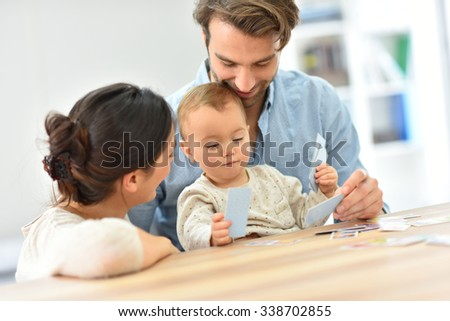 Parents with baby girl playing cards - stock photo