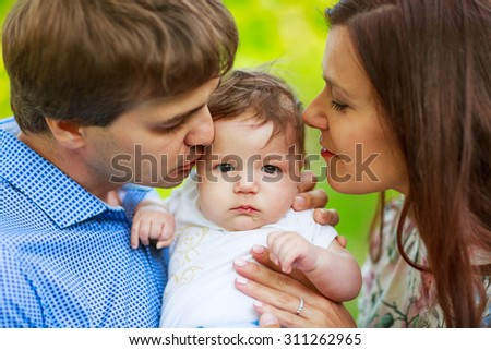 Parents with baby son, close-up, summer family photos outdoor - stock photo