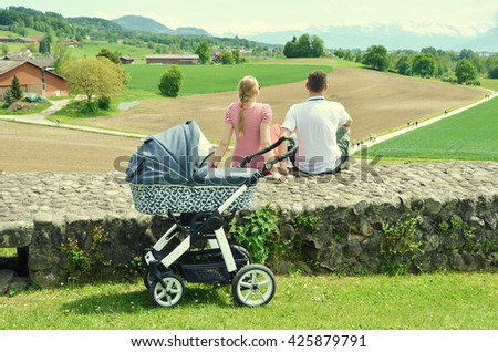 Parents with baby stroller enjoying Alpine panorama. Switzerland