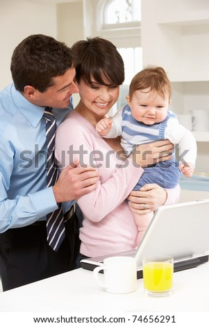 Parents With Baby Working From Home Using Laptop - stock photo