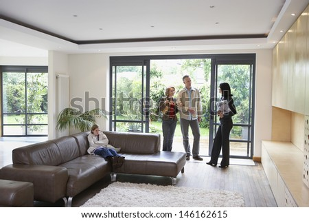 Parents with bored daughter and female estate agent at new property - stock photo
