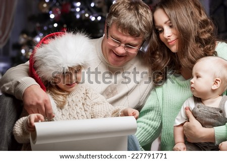 Parents with children are reading wish list to Santa Claus Christmas - stock photo