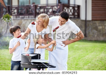 Parents with children at barbecue - stock photo