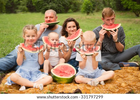 Parents with children eating watermelon in the park. Retro vintage instagram filter - stock photo