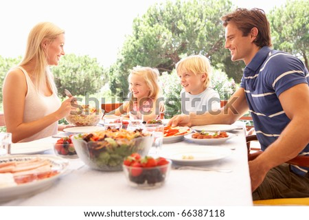 Parents, with children, enjoy a picnic - stock photo
