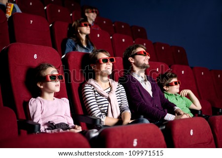 Parents with children enjoying time at the cinema - stock photo