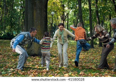 parents with children happily playing in autumn park