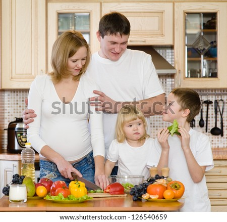 parents with children in kitchen - stock photo