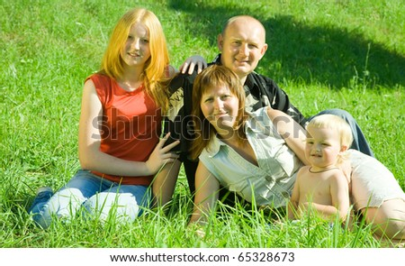 Parents with children lays in grass  at the park - stock photo