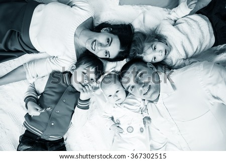 Parents with children lying on bed at home.  - stock photo