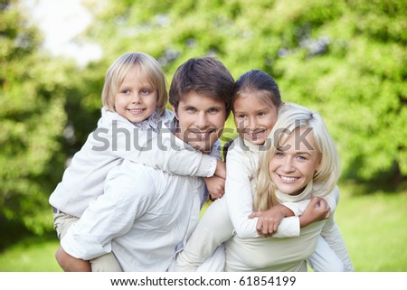 Parents with children on shoulders outdoors - stock photo