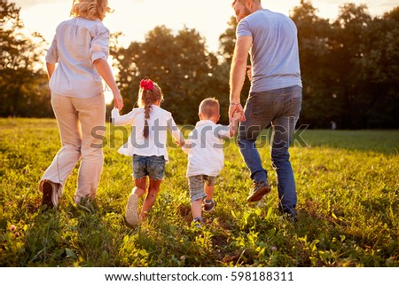 Parents with children walking in beautiful nature, back view
