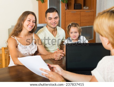 Parents with daughter glad hearing words of social worker with laptop - stock photo