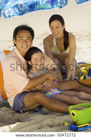 Parents with daughter (7-9) relaxing on beach, (portrait) - stock photo