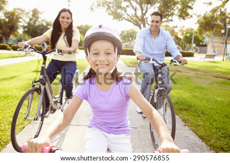 Parents With Daughter Riding Bikes In Park - stock photo