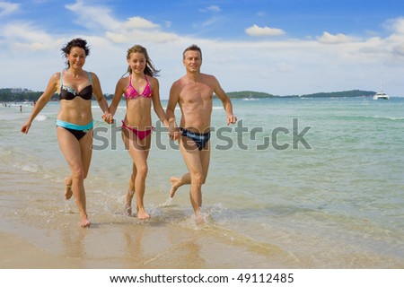 parents with daughter running at chaweng beach in samui island, thailand - stock photo