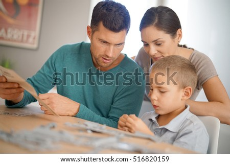 Parents with little boy building up model
