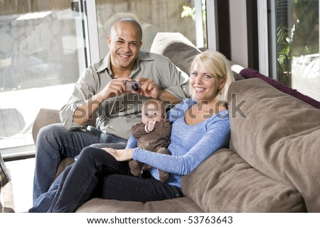Parents with 3 month old baby on lap at home, dad holding camera