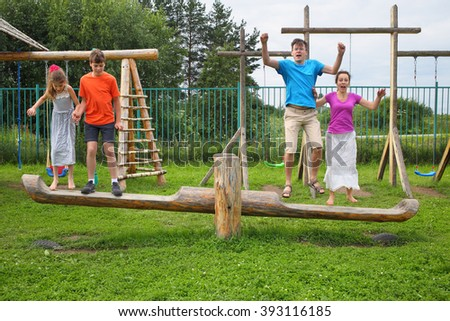 Parents with son and daughter jumping on a swing on a wooden playground