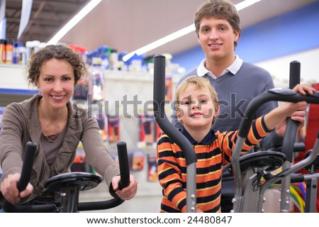 Parents with son  on sports training apparatus in shop, focus on boy - stock photo