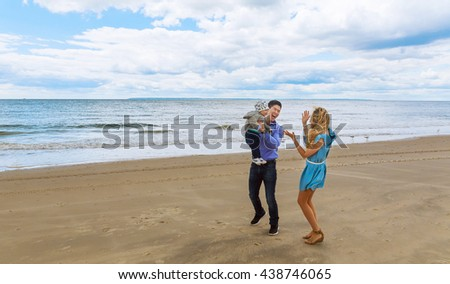 parents with son on the beach playing