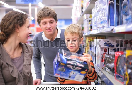 Parents with son with toy in shop, focus on father - stock photo