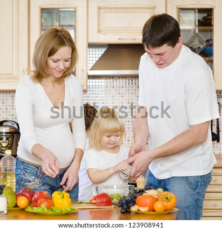 parents with the child in kitchen - stock photo
