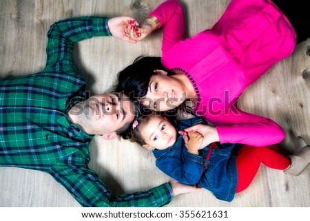 Parents with their 18 months old daughter, studio shot. - stock photo