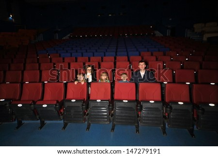 Parents with three children watching a movie in empty cinema hall  - stock photo