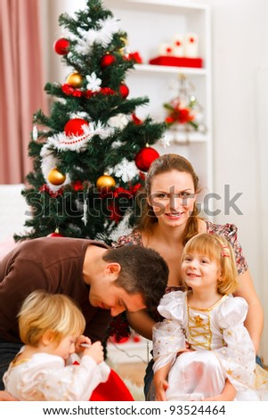 Parents with two daughters spending time near Christmas tree
