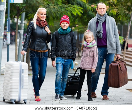 Parents with two kids and baggage chasing streets